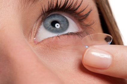 Close-up of blue woman eye with contact lens applying